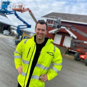 Bilde av Espen Løken hjemme på Gården Liftpartner driver, avbildet foran lifter og et rødt hus
